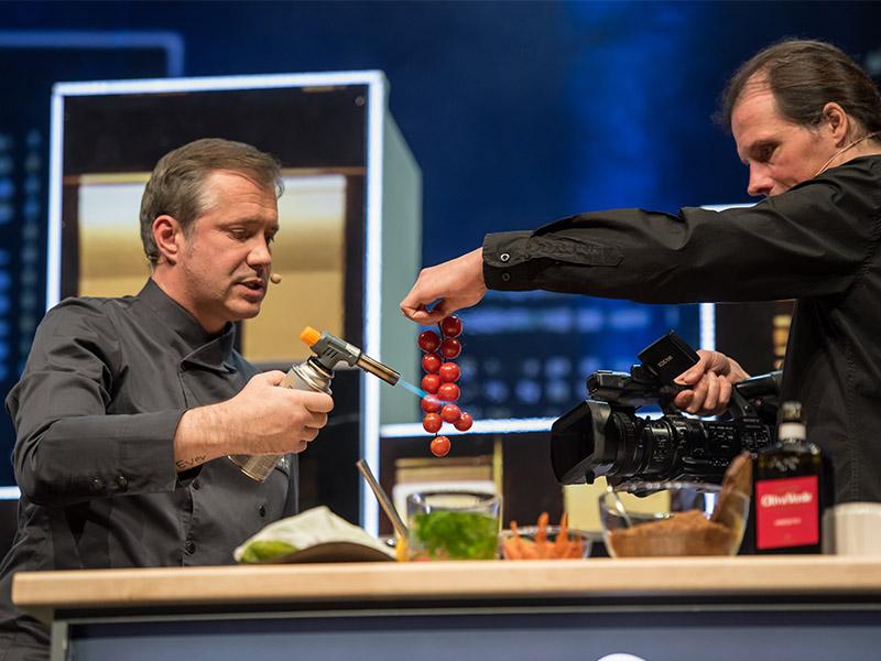 Alexander Herrmann auf der Bühne beim Flambieren von Tomaten.