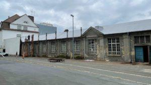Wo noch vor kurzem kalte Stahlbleche kühl auf den Betrachter herabblickten, erheben sich nun scheinbar aus der Zeit gefallene Fabrikhallen.